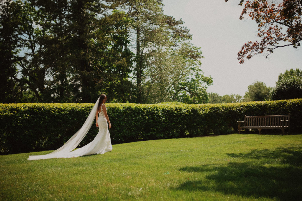editorial bride walking along hedges at the pine croft