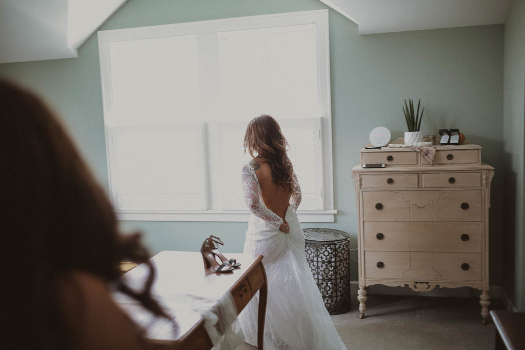 bride getting ready in front of window